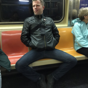Photo of an asshole in a leather jacket sitting on a subway seat with his legs spread out as far as they could possibly go.