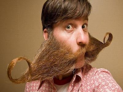 Homem jovem com barba e bigode em formatos muito exótico ou bizarro.