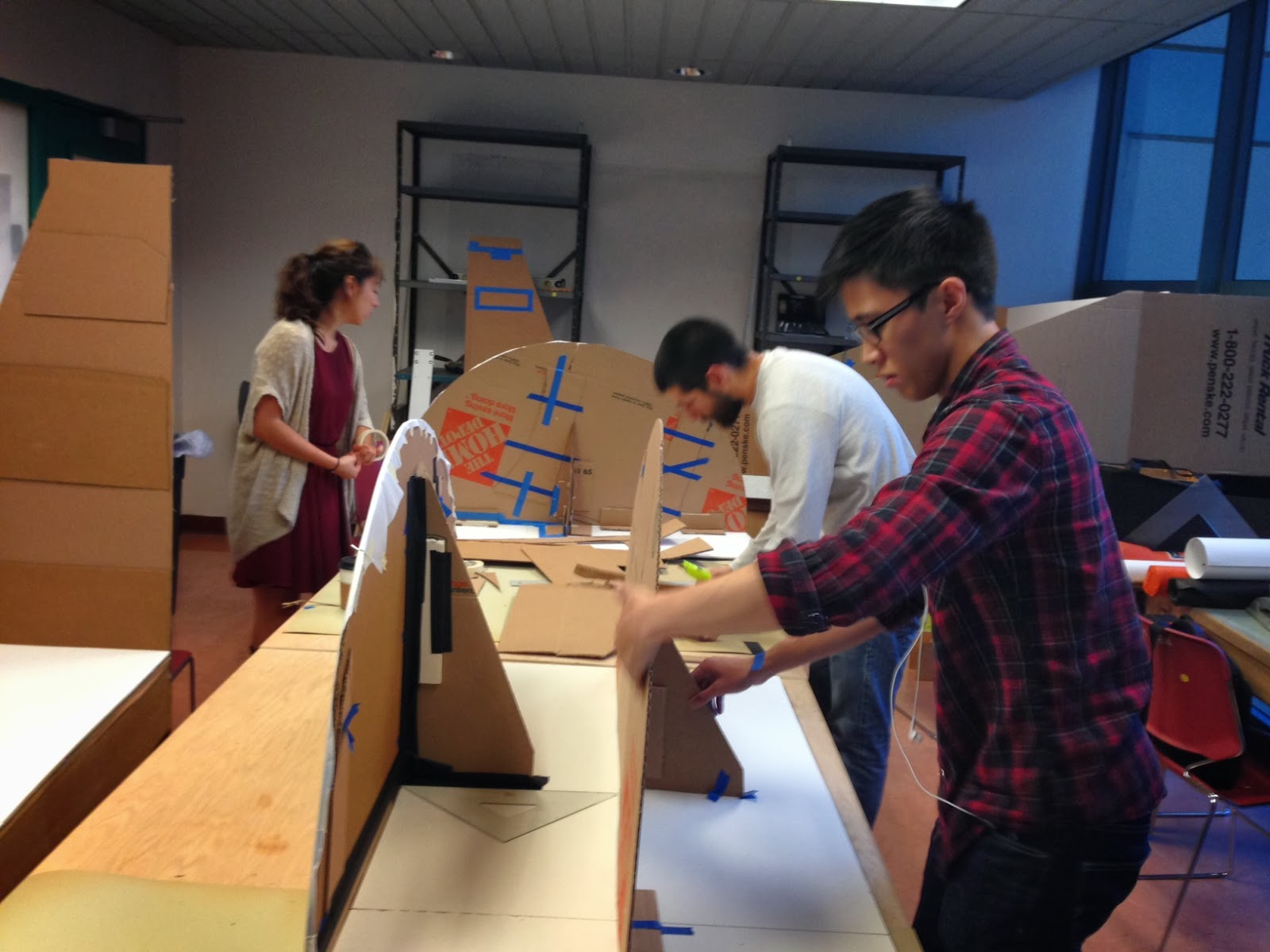 Students work on constructing the full-scale cardboard prototype. Pieces are scattered throughout the room to be assembled upon completion.