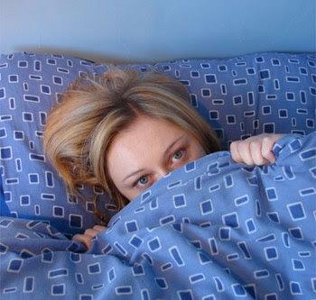 mulher timida deitada na cama debaixo das cobertas