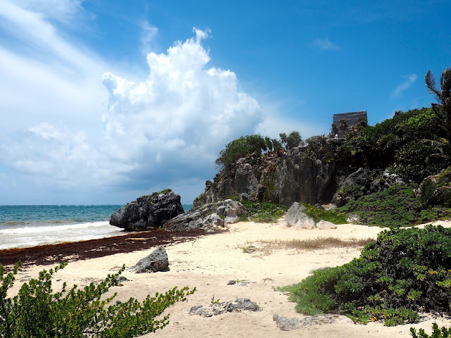 White sandy beach with Tulum ruins on the cliff in the background, Mexico