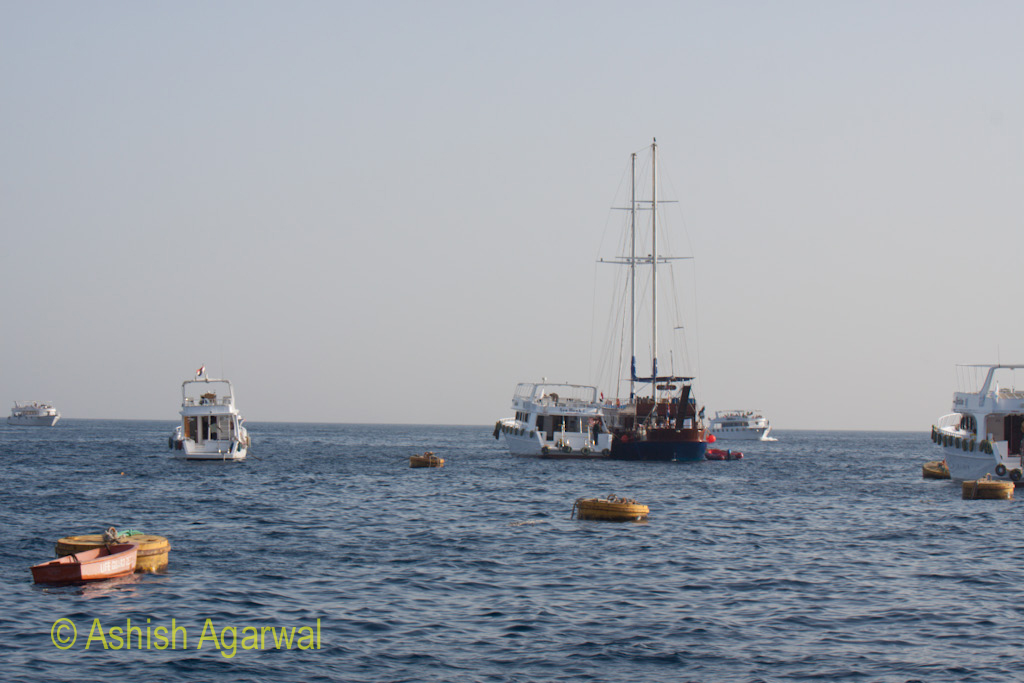 Boats headed out to the open sea and with smaller boats tied to buoys in the water
