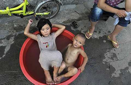 Children sit in a basin filled with water