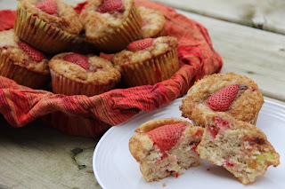 baked strawberry rhubarb muffins in a basket, with a muffin cut in half on a plate in front