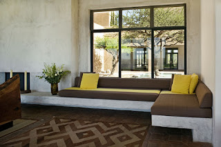 Appealing Brown Modern Sofa Bed near the Glass Windows and Concrete Wall on the Brown Floor