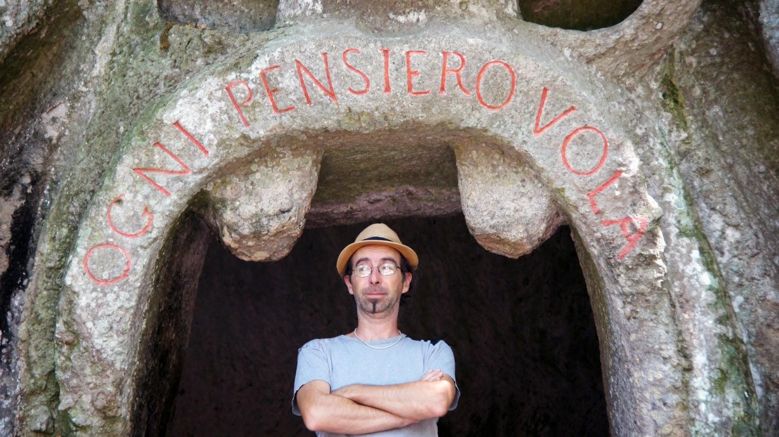 Sandro Pravisani sotto la scritta Ogni Pensiero Vola nel parco dei mostri a Bomarzo (VT)