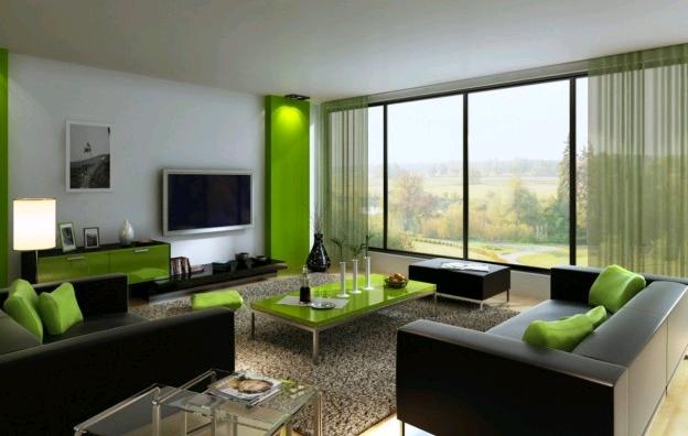 Arredi e complementi verdi nella zona giorno abbinati al grigio dei divani creano un ambiente elegante e soft
