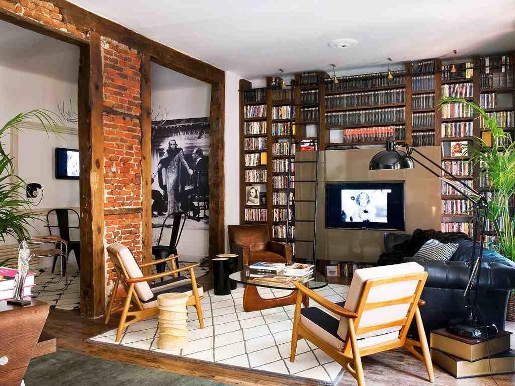 Ściana z cegłą z drewnianymi belkami Drewniany regał z kolekcją filmów, czarna sofa chesterfield