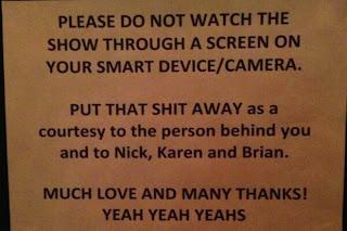 Foto de um cartaz com texto em inglês, pedindo ao público que aproveite o show, a tradução está logo abaixo.