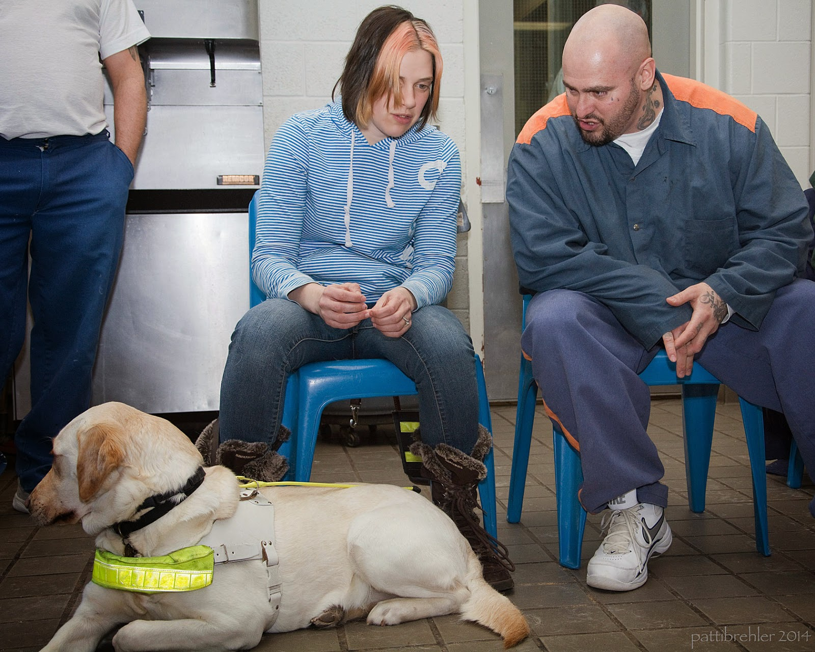 An adult yellow lab is lying on a light brown tile floor, facing to the left. She is wearing a neon yellow guide dog harness. A woman and a man are sitting on blue plastic chairs behind the dog. The woman, on the left, is wearing a long sleev blue and white striped shirt and blue jeans and furry winter boots. Her hair is brown and streaked with blonde in the front and is neck lenght. The man is wearing the blue and orange pirson uniform and white tennis shoes. He is bald and is leaning toward the woman in conversation. A man wearing a white t-shirt and blue pants is standing behine to the far left, mostly out of view.