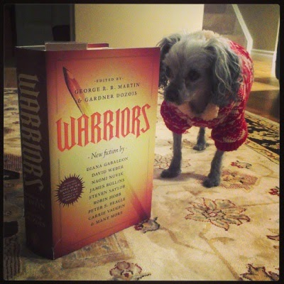 Murchie stands beside a hardcover copy of Warriors. He's wearing a thick, red and tan hoodie and he looks pretty durned nervous. The book is almost as tall as he is.