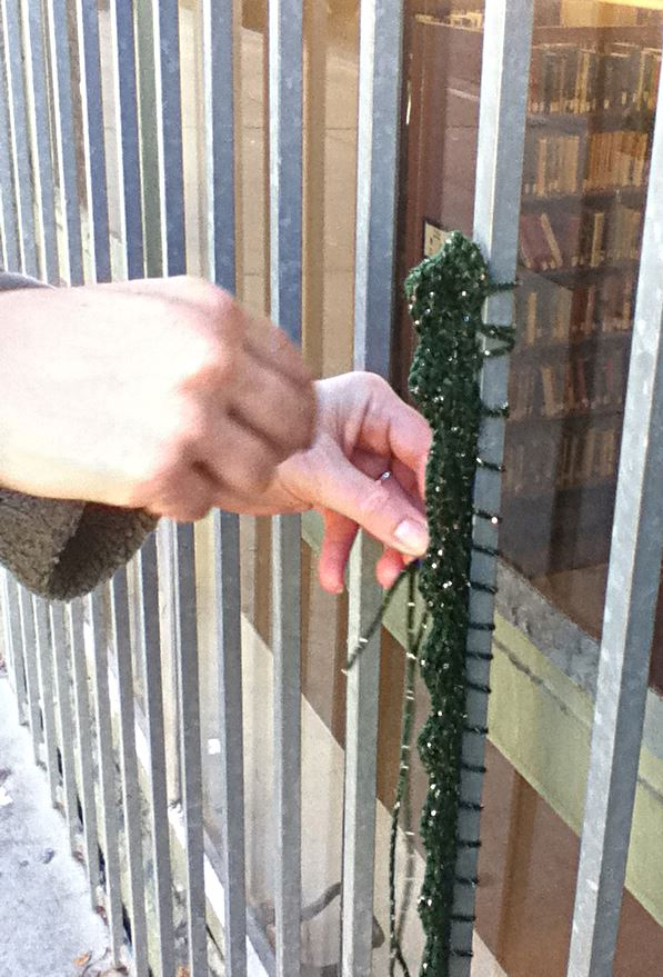 Attaching scallop tag to barred window at Berkeley Public Library