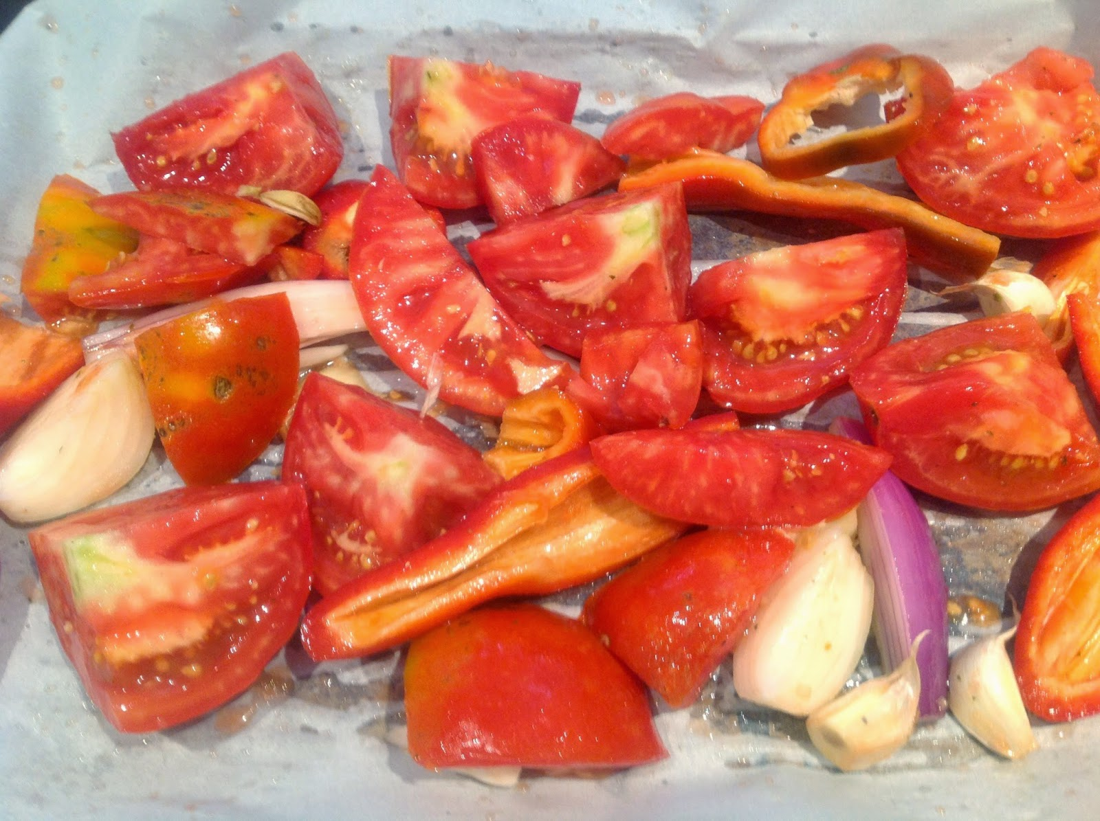 quartered tomatoes on a cookie sheet
