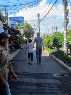 A tourist holds hands with a local Vietnamese man on a walk