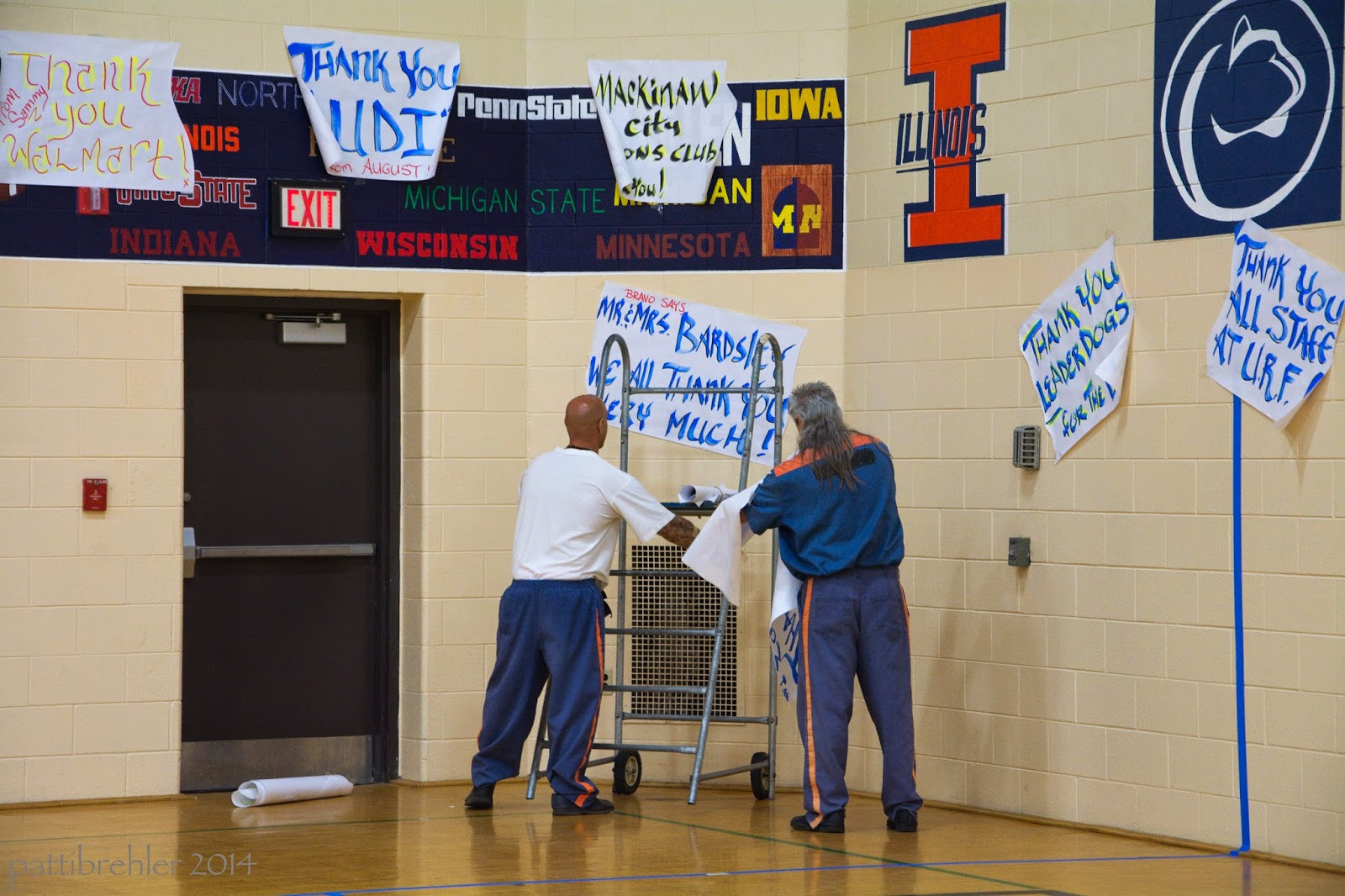 Two men, wearing blue prison uniforms (the man on the left is wearing a white t-shirt, are facing a gym wall. They are using a metal rolling ladder to tape posters on the wall.