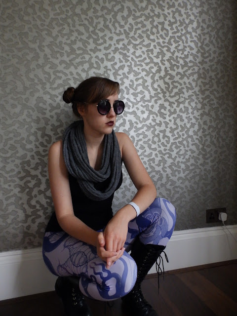 Fiona C (An Honest Drug is crouched in front of a mottled dark grey background. She is wearing a black tank top, black sunglasses, alien botany leggings, a grey snood, and knee high black lace up boots.