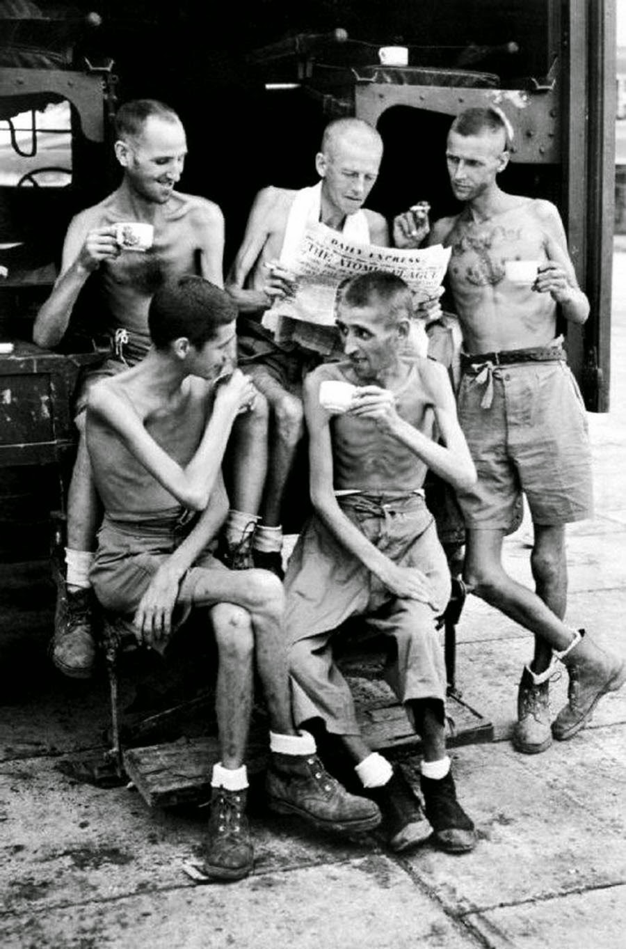 Five Australian former prisoners of war catch up on news from home after their release from Japanese captivity in Singapore, September 1945.