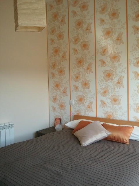 una de nuestras clientas sara ha decorado su dormitorio combinando un papel pintado de motivos florales en tonos naranja arena y blanco roto