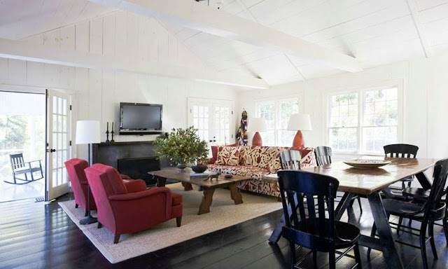 family room with trestle dining table, red sofa chairs, sisal rug, wall mounted television, vaulted ceiling beams, a fire place, french doors and a patterned sofa
