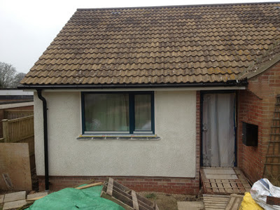 view of front door with neat new guttering above it