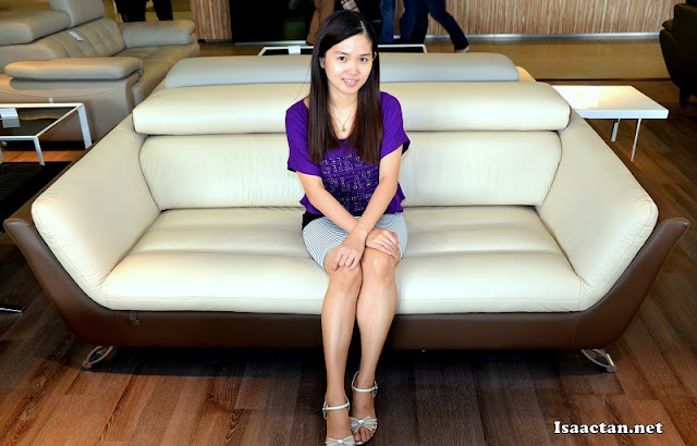 Janice happily posing for the camera sitting on one of the nicer looking sofas at Maju Home Concept