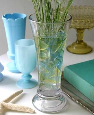 Add sea glass to a clear vase filled with water and flowers