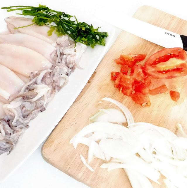 Calamares, tomate y cebolla en una tabla de madera sobre fondo blanco