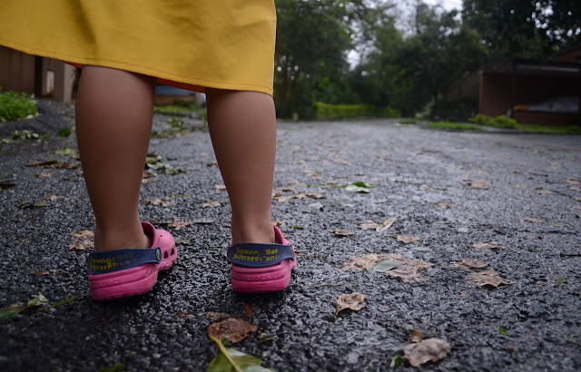 Kecil outside in her pink shoes and raincoat