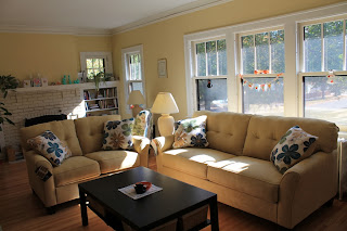 New yellow sofa and loveseat with flower pillows.