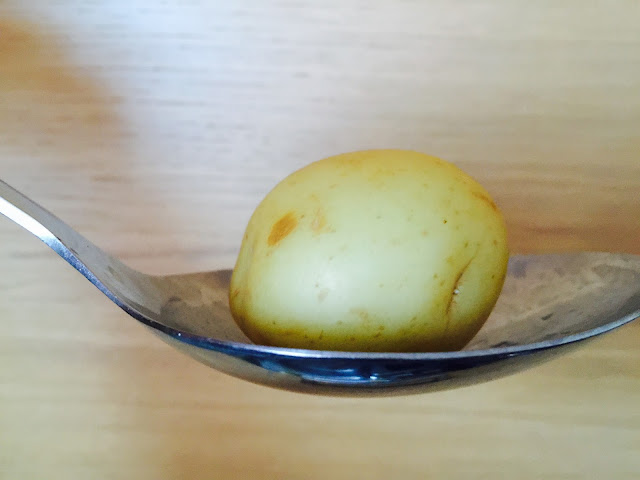 New potato in spoon