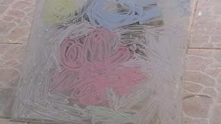 Szöveg: Ebben az üvegfestésben az a jó, hogy száradás után szimplán ujjal  újabb mintákat rajzolhatnak rá. Hátránya,hogy magas a baleseti kockázata: ablaktörés, ujjvágás. Kép: egy 25x40 centis ablakszemen krétáfestés: hatszirmú nagy bordó virág, zöld szárral, kék felhővel és sárga nappal.