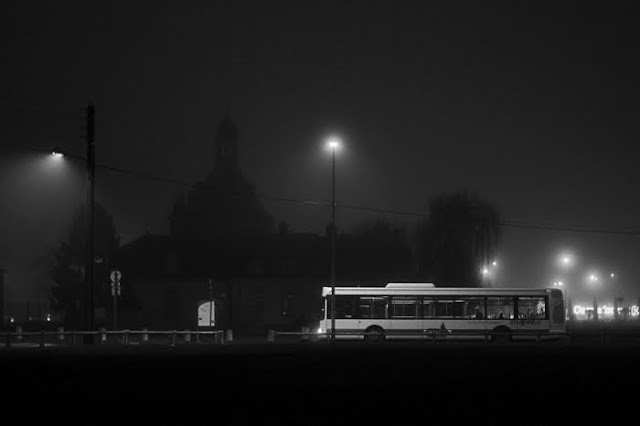 An image of the donjon of Sainte Genevieve des bois at night, in black and white, behind the fog with a bus in the first plan of the photo