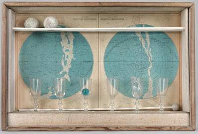 Glass box containing sat chart back, short glasses, marbles and xylophone malet