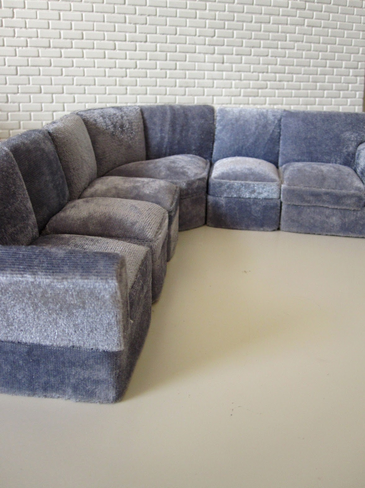 Modern miniature six seater grey velvet corner sofa.