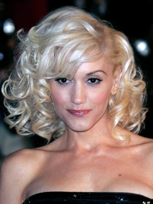 Gwen Stefani looks like a retro-inspired starlet with bouncy curls and fullness all over.