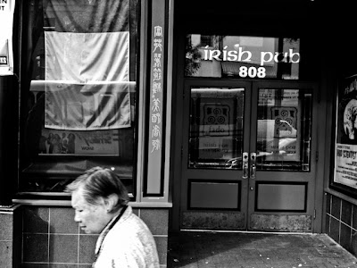 Asian woman walking past Irish Pub in Washington DC's Chinatown.
