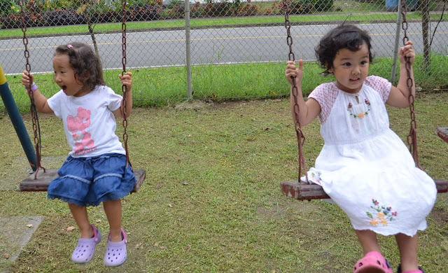 little girls side by side at the swing