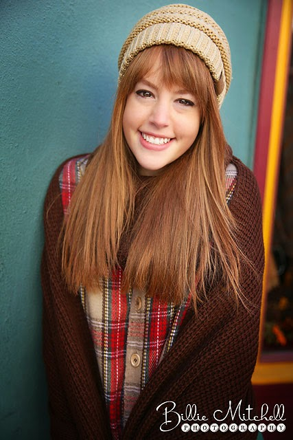 ginger girl wearing cream slouchy hat, brown knit wrap, and plaid tartan jacket