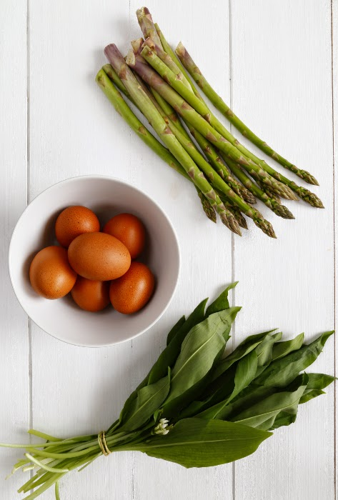Green asparagus, eggs and wild garlic on a white wooden background