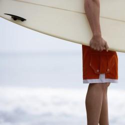 bras d'un homme qui porte une planche de surf