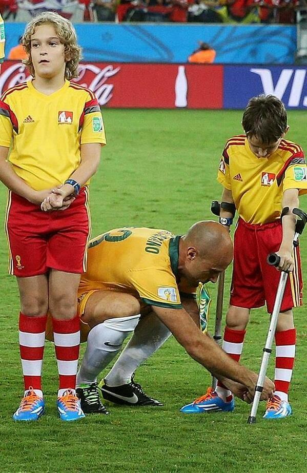 foto Pemain Bola Mark Bresciano, membetulkan tali sepatu seorang anak di lapangan hijau