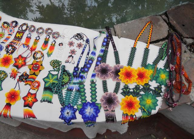 stand made on the rim of a fountain with lots of colourful traditional Mexican beaded necklaces