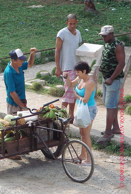 Una mujer compra comida en una carretilla de un cuenta-propista en La Habana, Cuba.