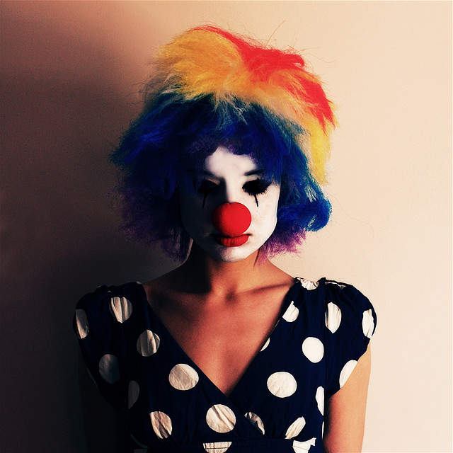 A sad look girl in a clown's wig and makeup