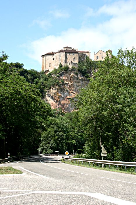 stone castles on cliff overlooking valley and modern road