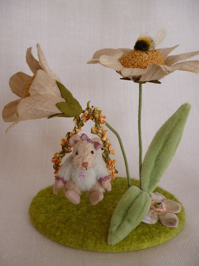 Tilly swinging from a hand sewn daisy made up of many French knots.