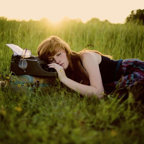 Jeune femme dormant sur sa machine à écrire.