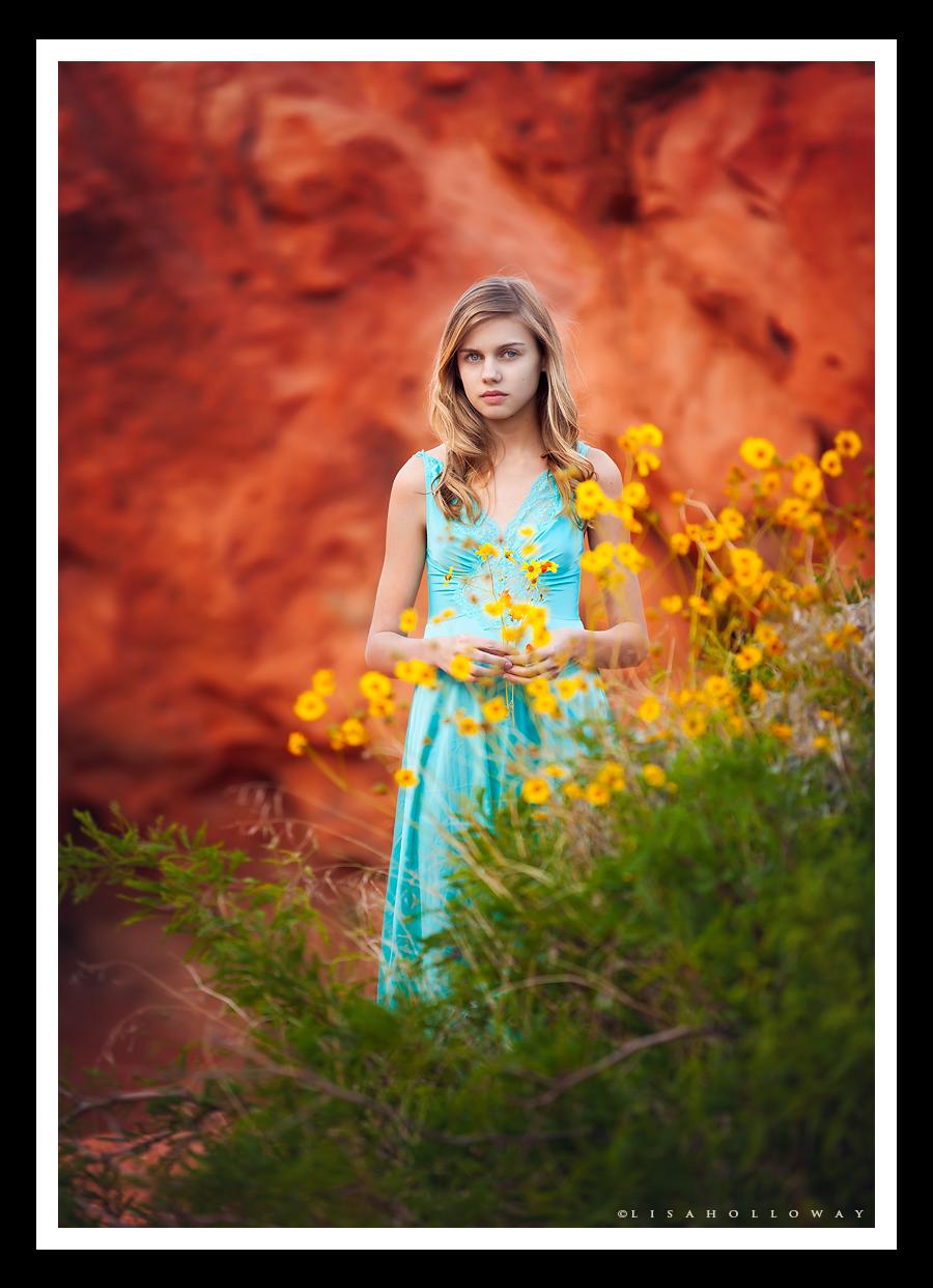 photo de Lisa Holloway représentant une jeune fille blonde derrière des fleurs jaunes