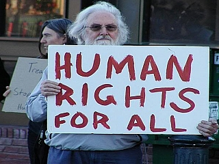 A man protesting holding a placard saying human rights for all