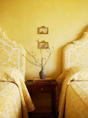 Bedroom with two twin beds with tall upholstered yellow brocade headboards